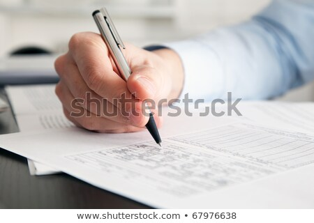 Closeup of a businessman's hand while writing some documents  Stock photo © Minervastock