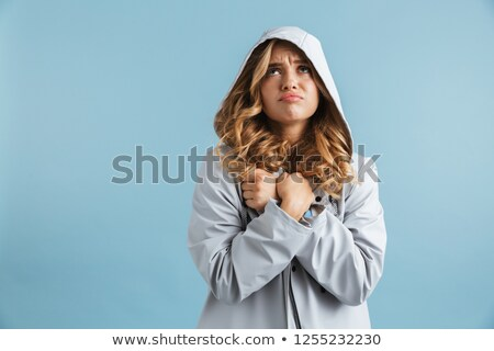 Image of upset woman 20s wearing raincoat with hood looking upwa Stock photo © deandrobot