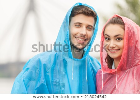 Image of cheerful woman 20s wearing yellow raincoat smiling at c Stock photo © deandrobot
