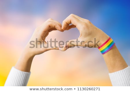woman with gay awareness wristband showing heart Stock photo © dolgachov