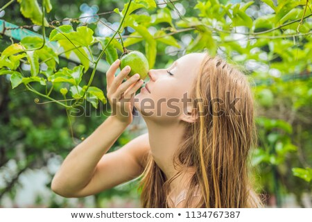 Young woman smelling the passion fruit in the garden Stock photo © galitskaya