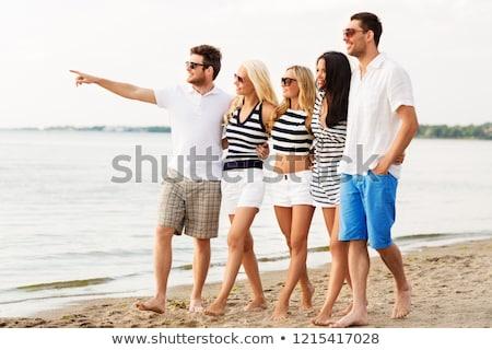 Barátok csíkos ruházat sétál tengerpart barátság Stock fotó © dolgachov