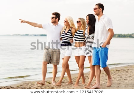 Amigos a rayas ropa caminando playa amistad Foto stock © dolgachov