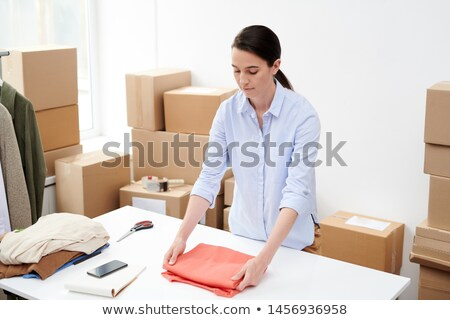 Pretty online shop manager preparing one of orders of clients Stock photo © pressmaster