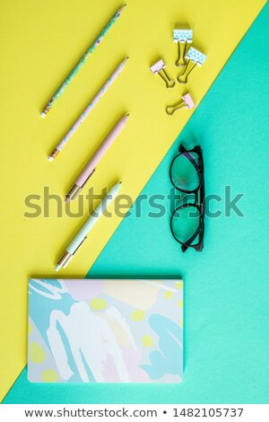 Overview of pens, clips, notebook and eyeglasses on yellow and blue background Stock photo © pressmaster