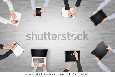 Group of people with devices in hands having desk discussion and Stock photo © ra2studio