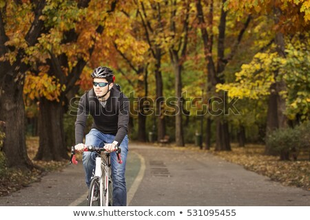 happy young man cycling by bicycle in summer park Stock photo © dolgachov