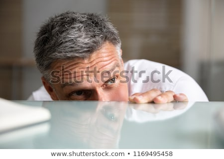 afraid businessman peeking from the edge of desk in office stock photo © andreypopov
