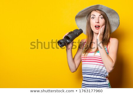 Stock photo: Shocked woman with a pair of binoculars