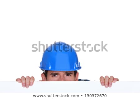 Builder peering over blank poster Stock photo © photography33