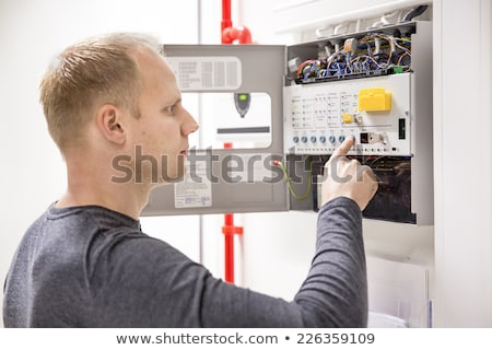 An electrician holding a fire alarm. Stock photo © photography33