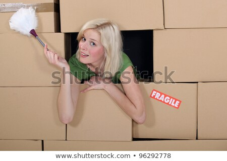 Woman with a feather duster surrounded by packing boxes Stock photo © photography33