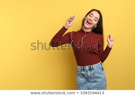derűs · fiatal · nő · zenét · hallgat · fejhallgató · szürke · nő - stock fotó © stockyimages