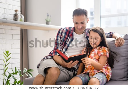 Foto stock: Young Father With His Little Daughter Reads The Bible
