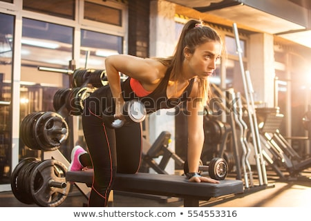 Stock photo: gym: portrait of  young woman lifting weights