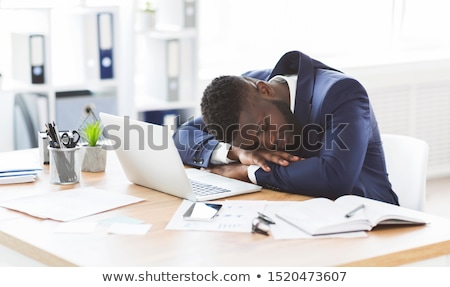 african man sleeping at his workplace in office stock photo © deandrobot