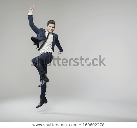 Young Businessman Jumping With Arms Raised Stock photo © AndreyPopov