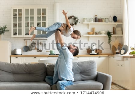 Happy parents together with a daughter with the hands lifted upwards a bright sunny day against the  stock photo © Paha_L