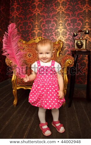 Little girl in red dress standing with red feather. Interior in retro style. Vertical format. Stock photo © Paha_L