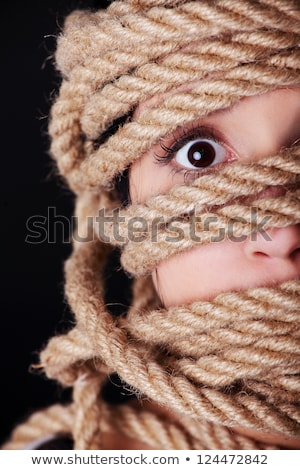 Portrait of scared young woman bounded with ropes Stock photo © deandrobot