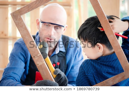 Stock photo: A boy hammering his head