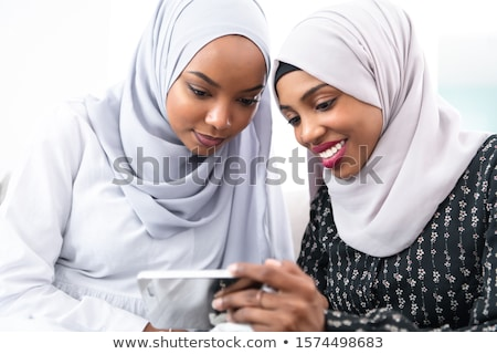 Portrait of beautiful smart young muslim woman wearing black hijab using virtual reality headset on  Stock photo © Traimak
