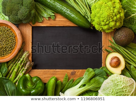 assorted green toned raw organic vegetables next to vintage chalk menu board avocado cabbage caul stock photo © denismart