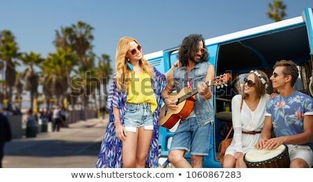 hippie friends playing music over minivan in la Stock photo © dolgachov