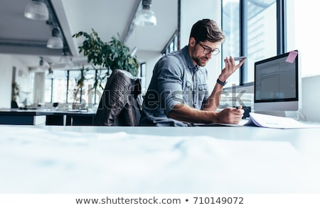 a young man sits in the office at a computer desk and holds a glass of coffee in his hand a young m stock photo © traimak