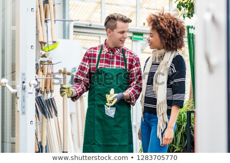 Handsome worker helping a customer with choosing a gardening tool Stock photo © Kzenon