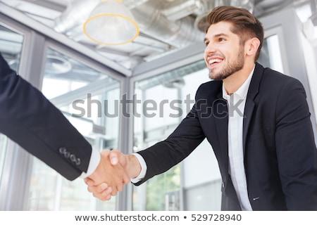 sonriendo · jóvenes · empresario · células · escribiendo - foto stock © deandrobot