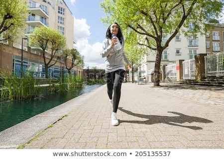 full length image of beautiful woman 20s drinking water and stan stock photo © deandrobot