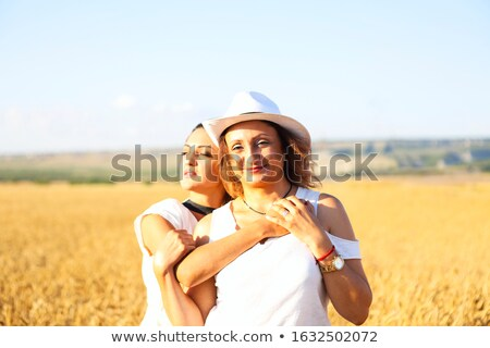 Middle age woman with her adult daughter wearing hat  Stock photo © dashapetrenko