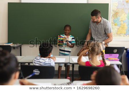 Front view of black schoolboy using maths abacus in classroom of elementary school Stock photo © wavebreak_media