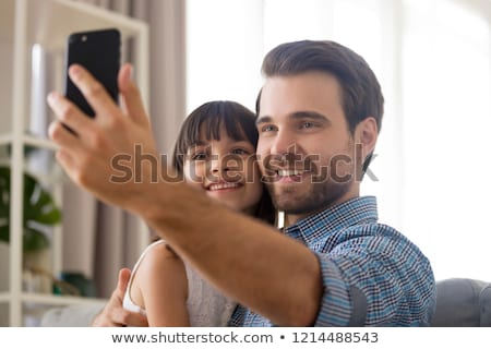 father photographing daughter by cellphone at home Stock photo © dolgachov