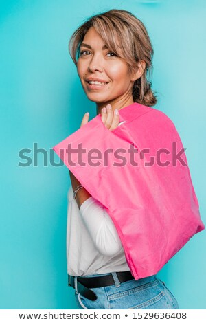 Stock photo: Young smiling woman in casualwear holding bright pink textile bag on shoulder