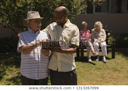 front view of senior friends discussing over digital tablet while sitting on sofa at home stock photo © wavebreak_media