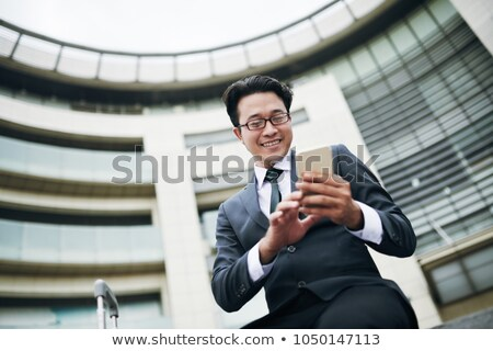 Low angle view of young Asian businessman using mobile phone during business seminar in office build Stock photo © wavebreak_media