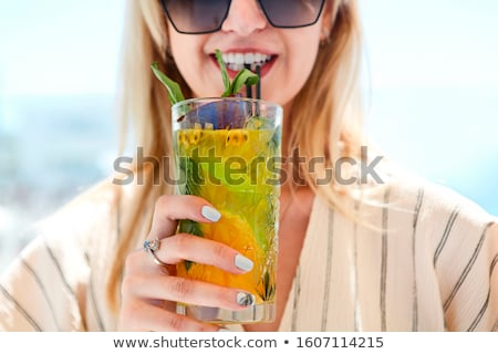 Woman holding a glass of passion fruit cocktail in Santorini bac Stock photo © dashapetrenko