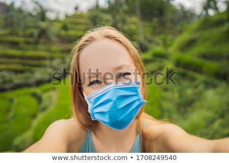 Beautiful young woman in medical mask walk at typical Asian hillside with rice farming, mountain sha Stock photo © galitskaya