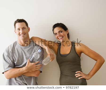 portrait of woman in fitness attire holding water bottle and smi Stock photo © dacasdo