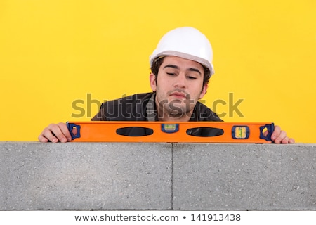 Man with spirit level on yellow background Stock photo © photography33