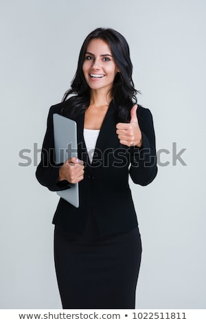 Woman standing while holding a laptop against white background Stock photo © wavebreak_media