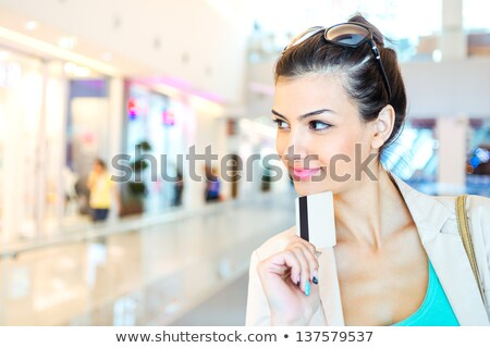 Attractive young woman with credit card looking away Stock photo © HASLOO