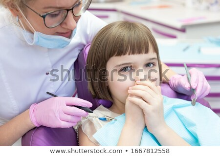 Terrified little girl looking at camera in dentists chair Stock photo © wavebreak_media