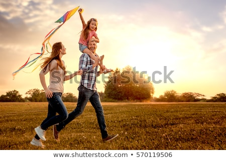 young woman and little girl plays kite on meadow stock photo © paha_l