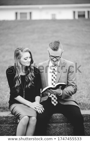 young couple male and female sitting in park and reading a book stock photo © zurijeta