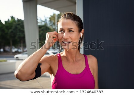Beautiful young fitness woman wearing armband with smartphone and earphones Stock photo © deandrobot