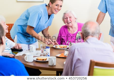 Idős idős férfi gondozó adag étel Stock fotó © godfer