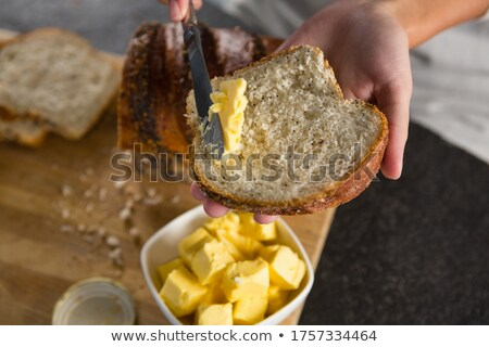 Woman applying butter over multigrain bread slice Stock photo © wavebreak_media